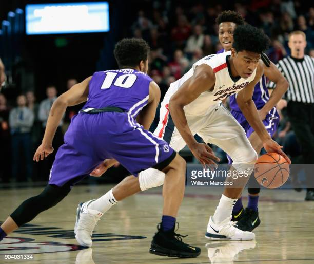 Rui Hachimura of the Gonzaga Bulldogs drives against Marcus Shaver Jr #10 of the Portland Pilots in the second half at McCarthey Athletic Center on...