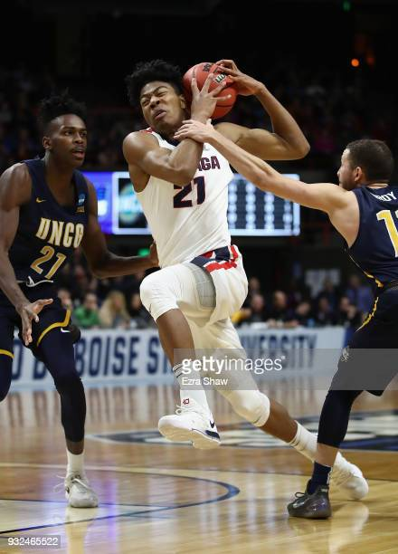 Rui Hachimura of the Gonzaga Bulldogs drives to the basket against James Dickey and Demetrius Troy of the UNCGreensboro Spartans in the first half...