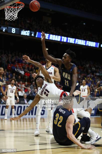 Rui Hachimura of the Gonzaga Bulldogs falls as he shoots the ball against James Dickey and Jordy Kuiper of the UNCGreensboro Spartans in the first...