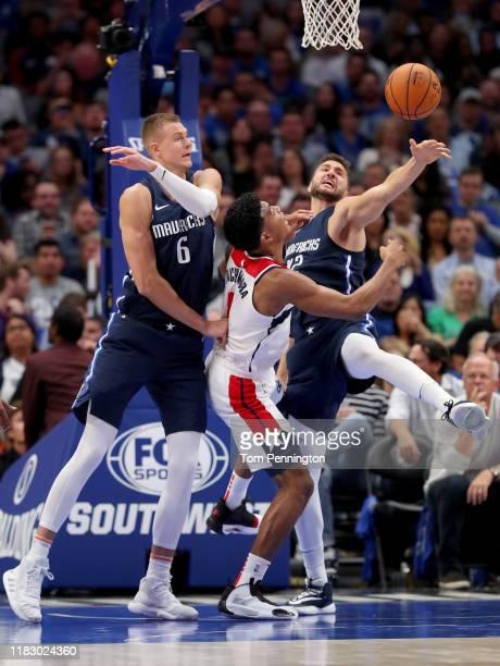 Rui Hachimura of the Washington Wizards drives to the basket against Kristaps Porzingis of the Dallas Mavericks and Maxi Kleber of the Dallas...
