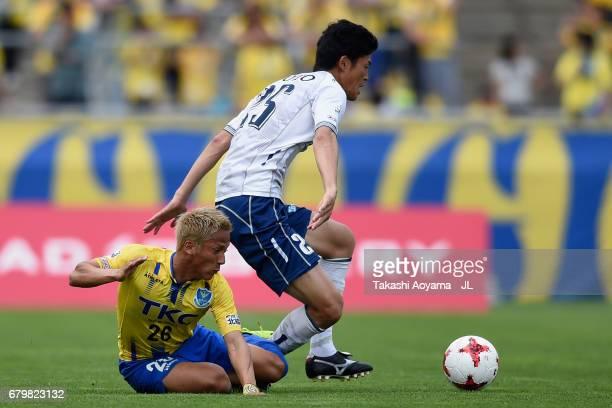 Rui Komatsu of Giravanz Kitakyushu is challenged by Ryosuke Tada of Tochigi SC during the J.League J3 match between Tochigi SC and Giravanz...
