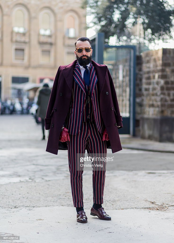 Rui Martins is wearing a bordeaux coat, striped suit, gloves, leather shoes, sunglasses, tie on January 10, 2017 in Florence, Italy.