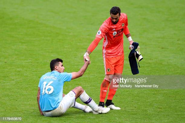 Rui Patricio of Wolverhampton Wanderers helps up a dejected Rodrigo of Manchester City during the Premier League match between Manchester City and...