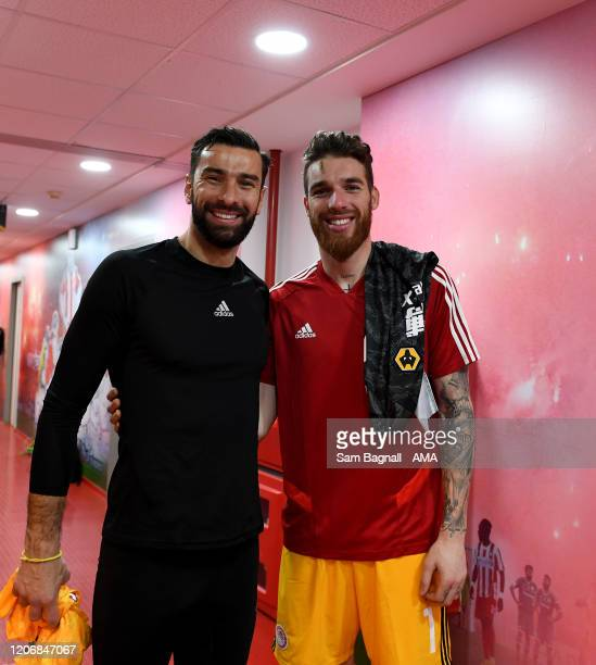 Rui Patricio of Wolverhampton Wanderers speaks with fellow Portugal goalkeeper Jose Sa of Olympiacos FC after the UEFA Europa League round of 16...