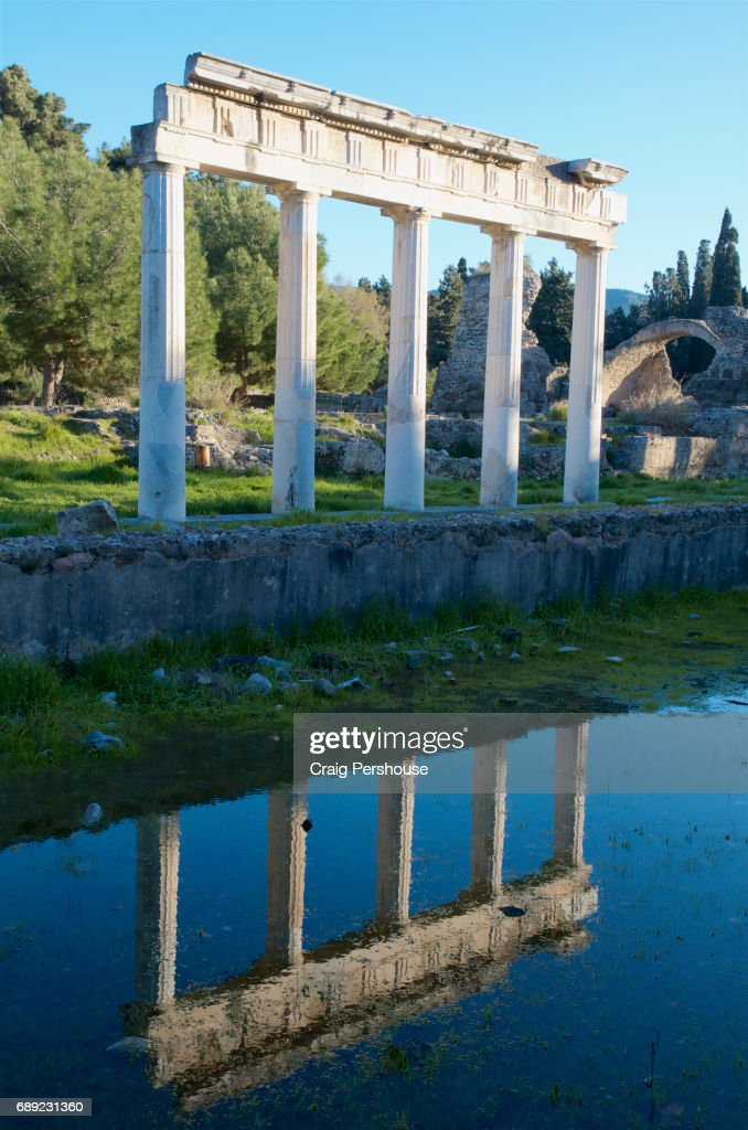 Ruined colonnade reflected in pond, in the western excavation site. : Stock Photo