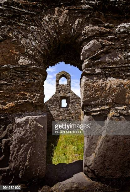 ruined grey stone old celtic church viewed through a stone arch - isle of man stock pictures, royalty-free photos & images