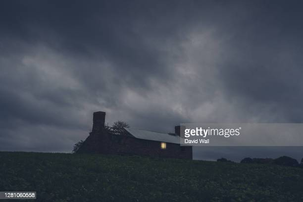 a ruined house in the middle of the countryside. with a light shining from a broken window on a stormy night - cloud sky stock pictures, royalty-free photos & images