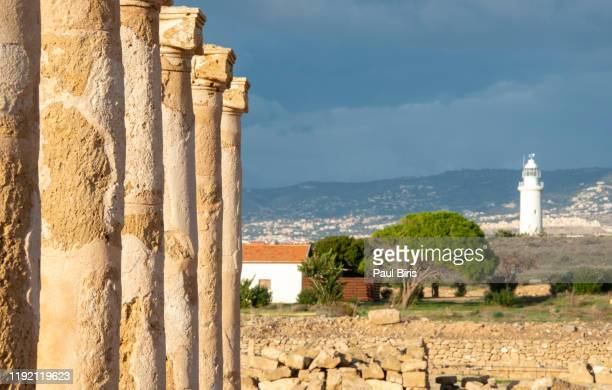 ruins at the archaeological helenistic and roman site at kato paphos in cyprus with old white lighthouse in the background - パフォス考古学公園 ストックフォトと画像