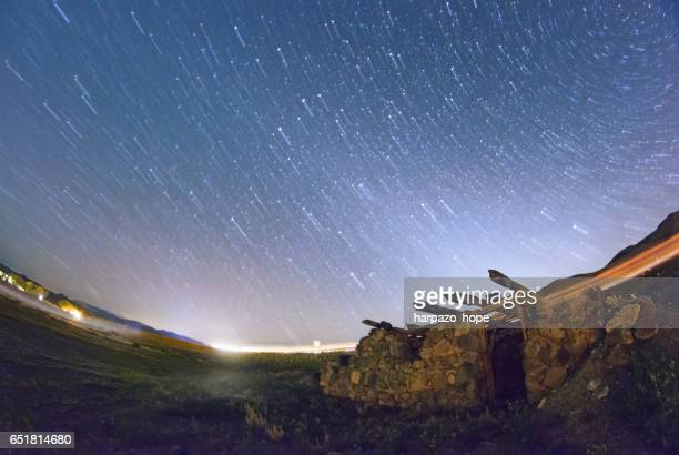 Ruins of a stone building under a starry sky with light trails.