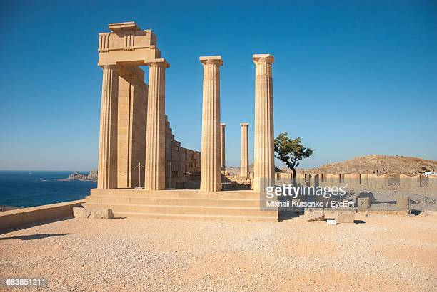 ruins of ancient temple against clear blue sky - greek culture stock pictures, royalty-free photos & images