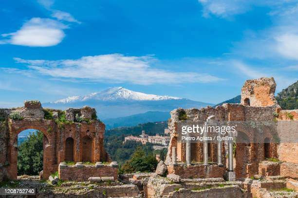 ruins of building against cloudy sky - taormina stock pictures, royalty-free photos & images