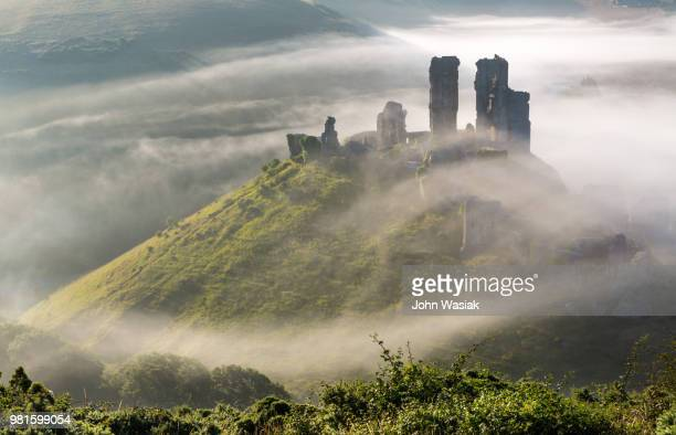 Ruins of Corfe castle on hill in fog, Dorset, England, UK