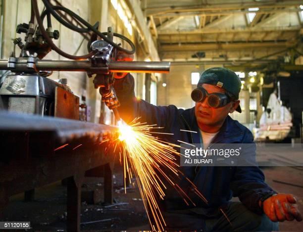 Ruiz Fortunato, a worker of the Rio Santiago shipyard cuts a steel sheet in Ensenada La Plata , Argentina, 26 July 2004. Rio Santiago, the biggest...