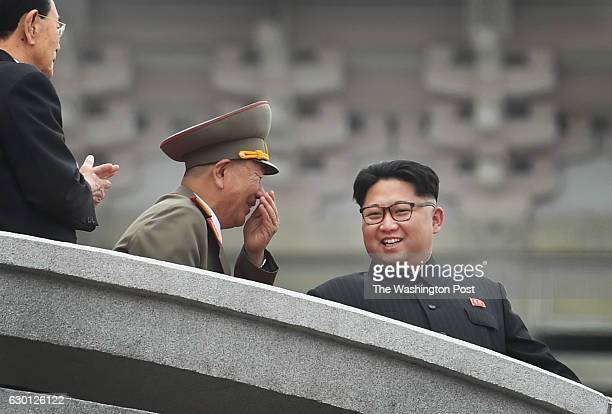 Ruler Kim Jong Un has and exchange with an advisor during a parade at Kim Il Sung Square in Pyongyang North Korea on May 10 2016 The parade and...