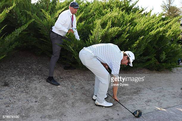 A rules official helps golfer Seamus Power of Ireland locate his drop point out of the rough during the second round of the Utah Championship...