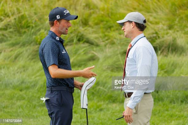Rules official returns returns Webb Simpson of the United States his driver on the 12th hole during a suspension in play during the second round of...
