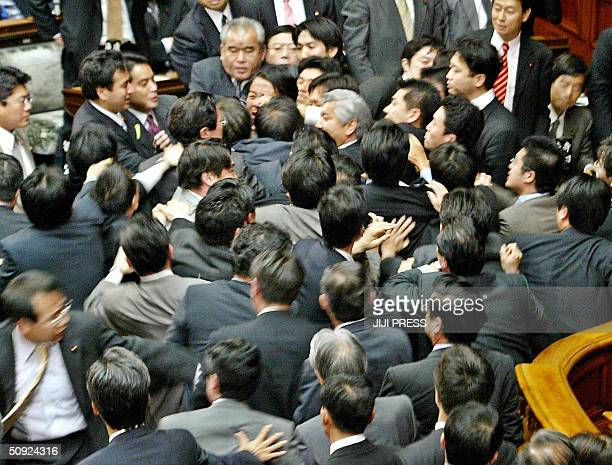 Ruling and opposition lawmakers scuffle at the plenary session of the Lower House at the National Diet in Tokyo 04 June 2004 Japan's parliament was...