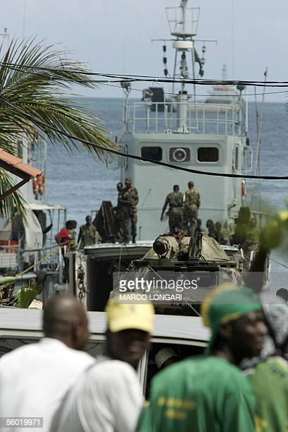 Ruling Chama Cha Mapinduzi supporter heading for a rally pass by a pier where Tanzanian soldiers supervise the arrival of an APC from a military...