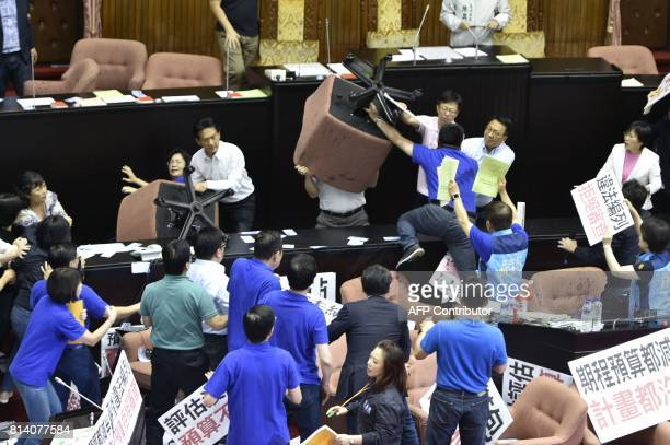 Ruling Democratic Progressive Party legislators Cheng Yunpeng and Wu Pingjui brandish chairs while facing demonstrating main opposition Kuomintang...