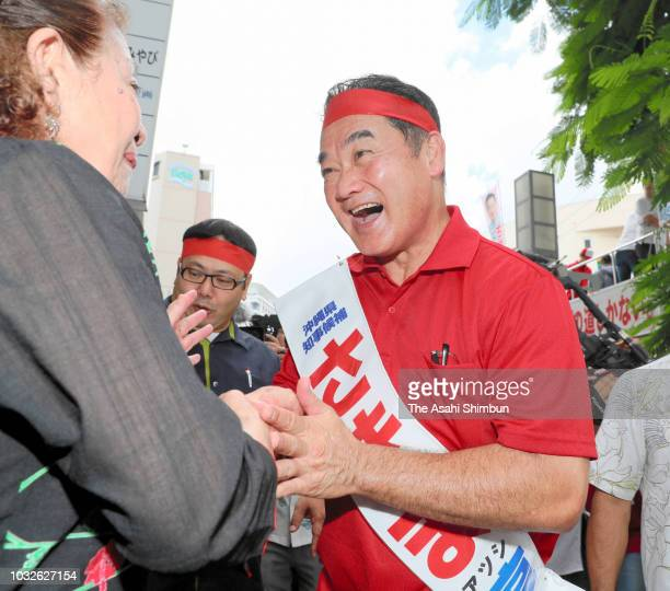 Ruling Liberal Democratic Party backed candidate Atsushi Sakima shakes hands with his supporter as the Okinawa gubernatorial election officially...