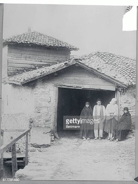 Rumania: Photo shows Queen Marie of Rumania in national garb pointing with some of her subjects in front of their unpretentious home at Balcic. Note...