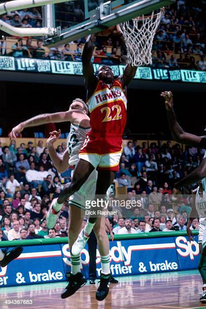 Rumeal Robinson of the Atlanta Hawks dunks the ball against Larry Bird of the Boston Celtics during a game played in 1992 at the Boston Garden in...