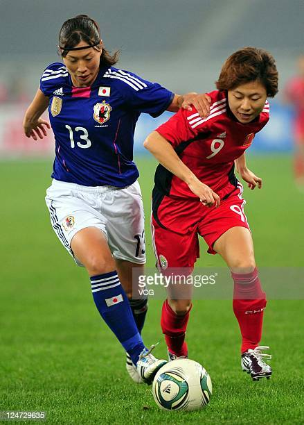 Rumi Utsugi of Japan and Xu Yuan of China compete for the ball during the London Olympic Women's Football Asian Qualifier match between Japan and...