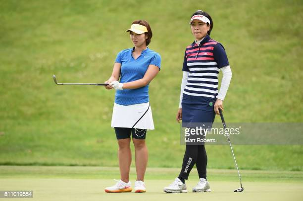 Rumi Yoshiba of Japan speaks with Shiho Oyama of Japan on the 15th green during the final round of the Nipponham Ladies Classics at the Ambix...