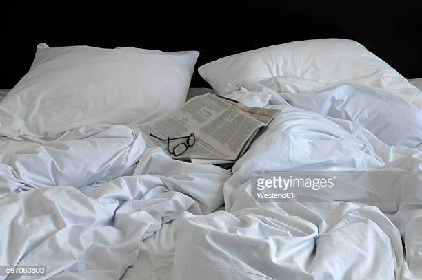 Rumpled bed with glasses and newspaper