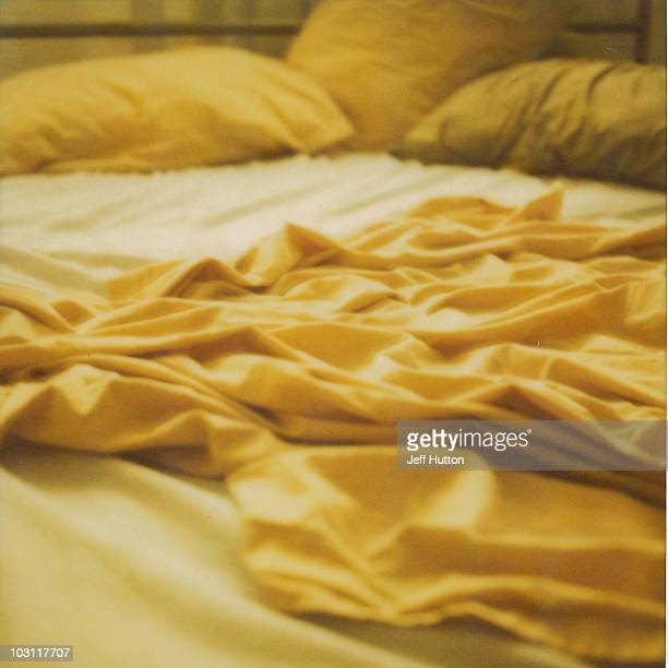 rumpled bed, yellow sheets - hutton stock photos and pictures