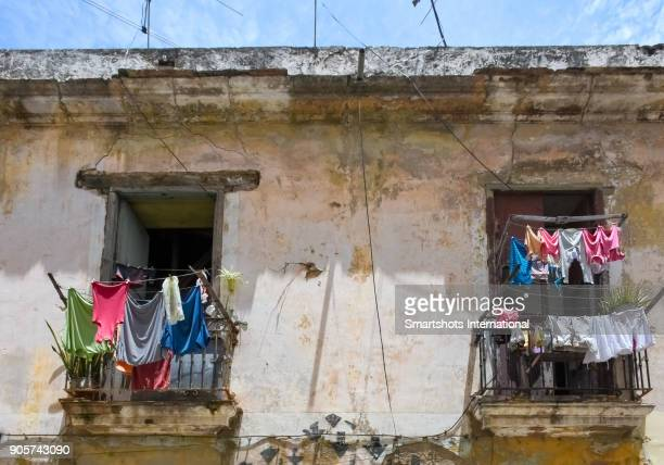 Run down building in old Havana with laundry drying and hanging in balcony, Cuba