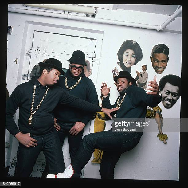 RunDMC a hip hop rap group pose in front of a wall with images of jazz musicians Rappers Run Joe Simmons and DMC Darryl McDaniels make up the group...