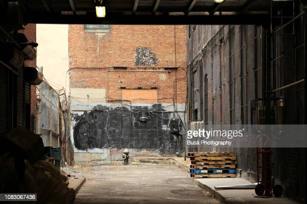 run-down back alley with fire hydrant against industrial wall. new york city - cul de sac stock pictures, royalty-free photos & images