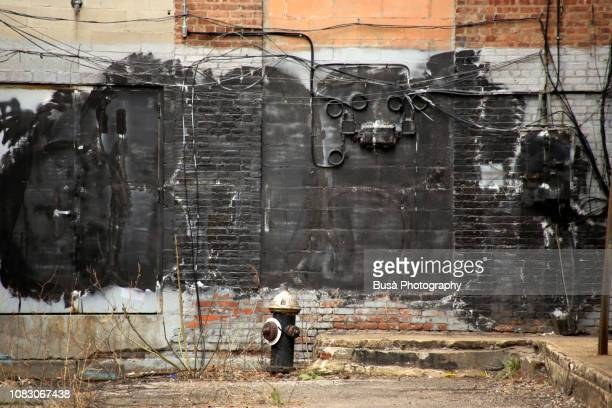 Run-down back alley with fire hydrant against industrial wall. New York City