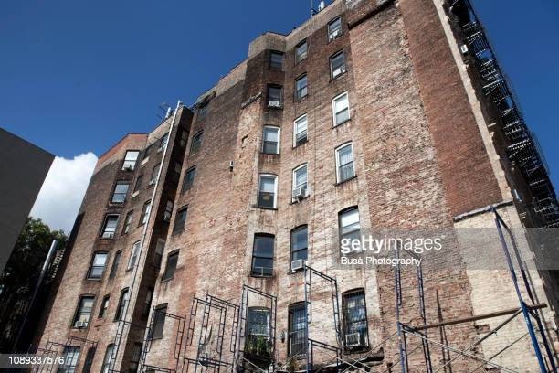 run-down facade of tenement building in the east village with scaffolding. manhattan, new york city, usa - east village stock pictures, royalty-free photos & images
