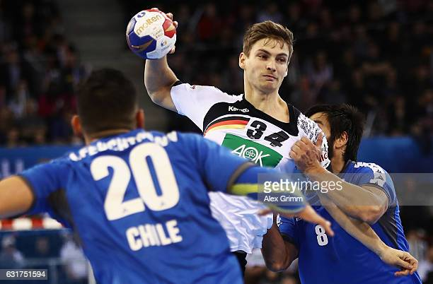 Rune Dahmke of Germany is challenged by Eric Kaniu of Chile during the 25th IHF Men's World Championship 2017 match between Chile and Germany at...