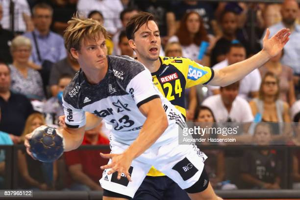 Rune Dahmke of Kiel battles for the ball with Patrick Groetzki of RheinNeckar Loewen during the Pixum DHB Handball Super Cup 2017 between RheinNeckar...