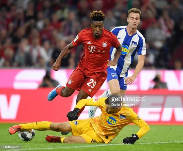 Rune Jarstein of Hertha BSC tackles Kingsley Coman of FC Bayern Munich during the Bundesliga match between FC Bayern Muenchen and Hertha BSC at...