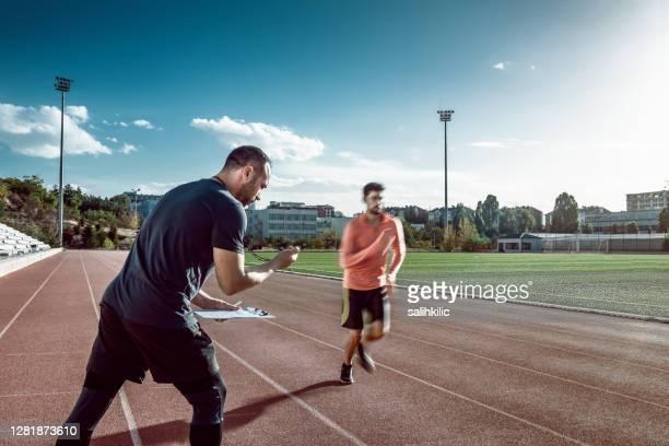 löpare och tränare gör sportträning på friidrott. coachen mäter resultat med ett stoppur - coach bildbanksfoton och bilder