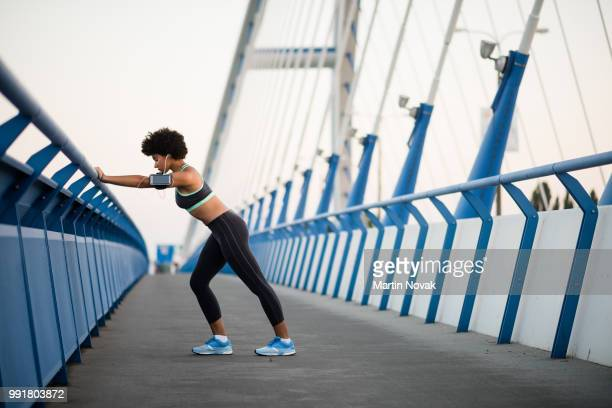 Runner athlete running at city bridge. Jogging and workout concept.