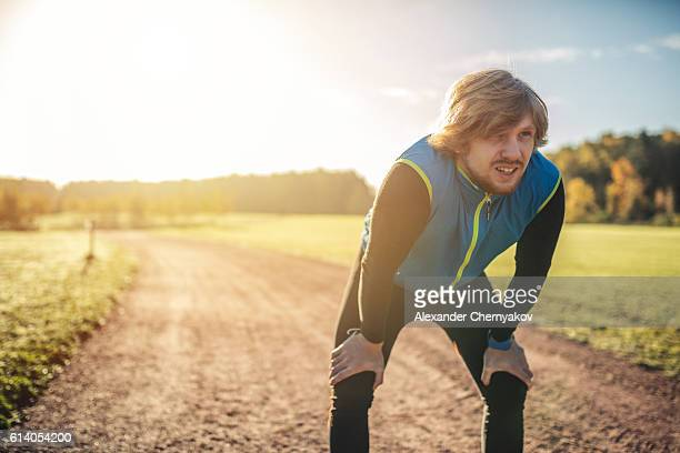 runner breathing while taking a break from exercise - toughness stock pictures, royalty-free photos & images