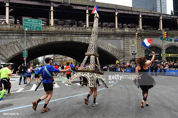 A runner carries a model of Eiffel Tower during the TCS New York City Marathon in New York on November 1 2015 / AFP / JEWEL SAMAD