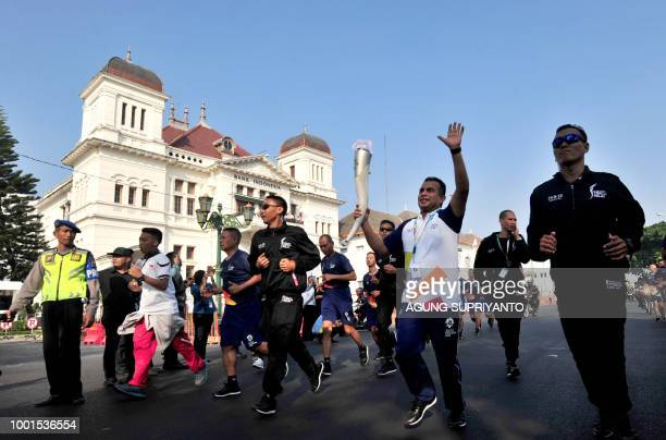 A runner carries the torch of the Asian Games during a torch relay in Yogyakarta on July 19 2018 Jakarta and Palembang in Sumatra are set to host...