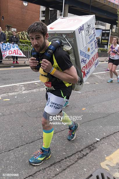 A runner carrying a washing machine takes part in the 2016 London Marathon in London United Kingdom on April 24 2016