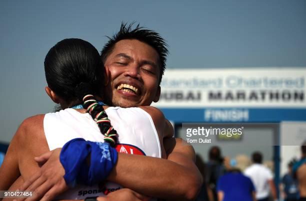 A runner celebrates finishing the Standard Chartered Dubai Marathon on January 26 2018 in Dubai United Arab Emirates