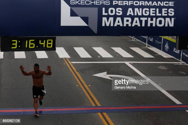 A runner celebrates while crossing the finishing line in the 32nd annual Los Angeles Marathon in Santa Monica on March 16 2017