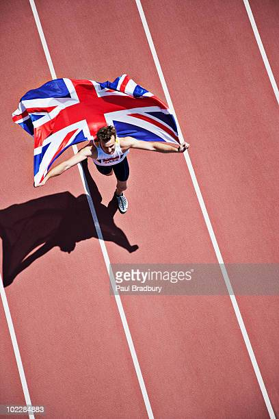 runner celebrating with british flag on track - lap of honour stock pictures, royalty-free photos & images