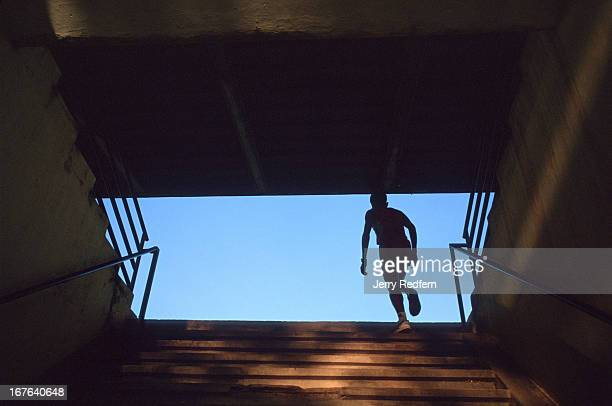 A runner climbs the stairs to the old Olympic Stadium in Phnom Penh following a workout