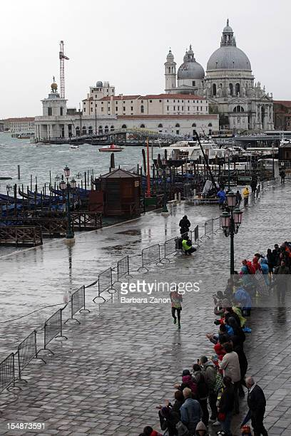 A runner competing in the Venice Marathon arrives during high tide at San Marco Square on October 28 2012 in Venice Italy Starting from Stra the...