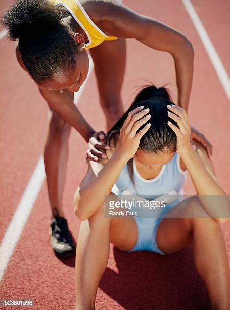 runner consoling another runner on track - derrota imagens e fotografias de stock